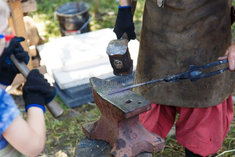 forja O ferreiro processa o metal caloroso com um malho no batente Trabalho manual de um ferreiro fotografia de stock