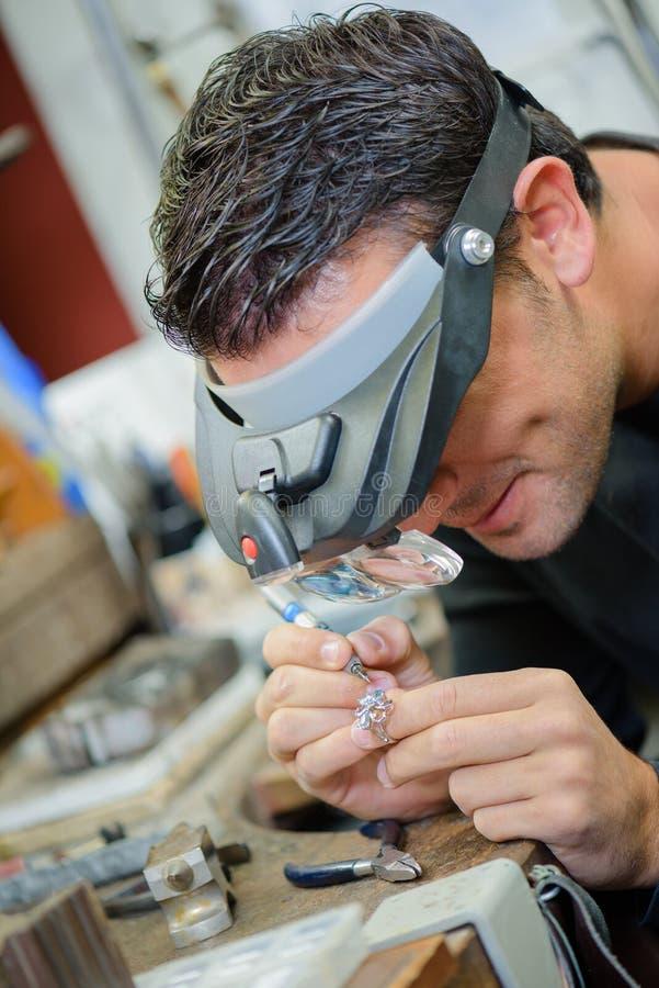 Forjador de plata que trabaja con la luz corta foto de archivo libre de regalías