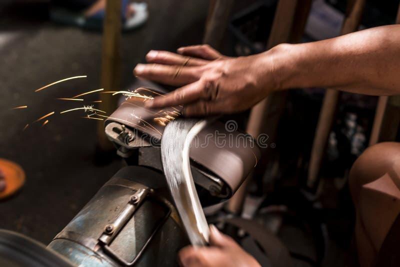 Forjador del metal que afila las herramientas y los cuchillos de la granja foto de archivo libre de regalías