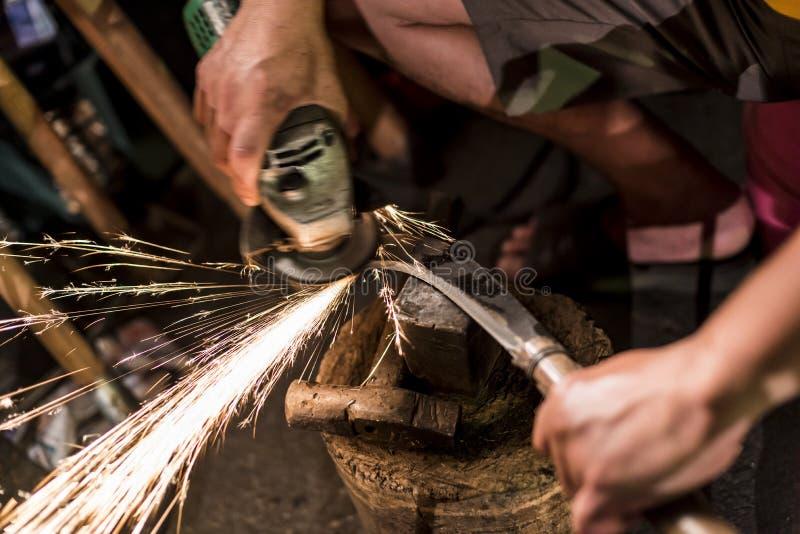 Forjador del metal que afila las herramientas y los cuchillos de la granja imagen de archivo libre de regalías