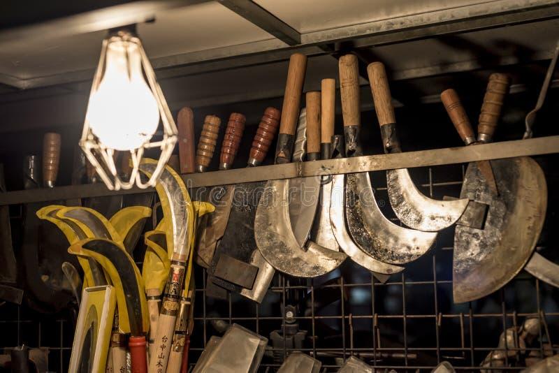 Forjador del metal que afila las herramientas y los cuchillos de la granja imagen de archivo