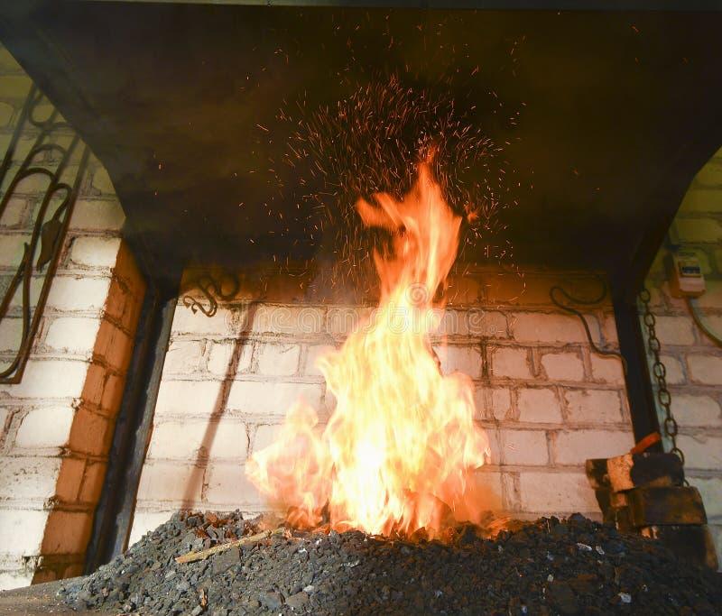 Forje o fogo no ferreiro onde as ferramentas do ferro crafted foto de stock