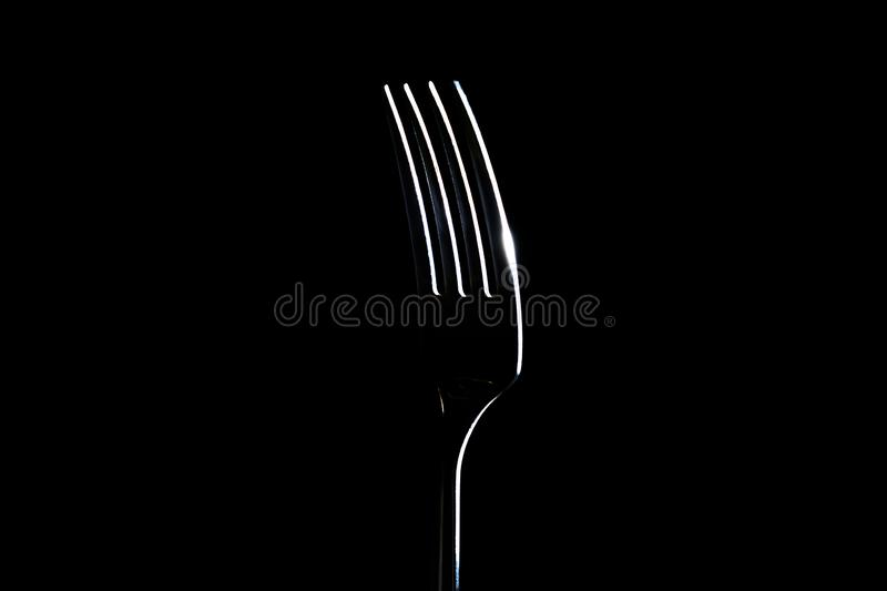 Fork on a black background with light from the side stock photo