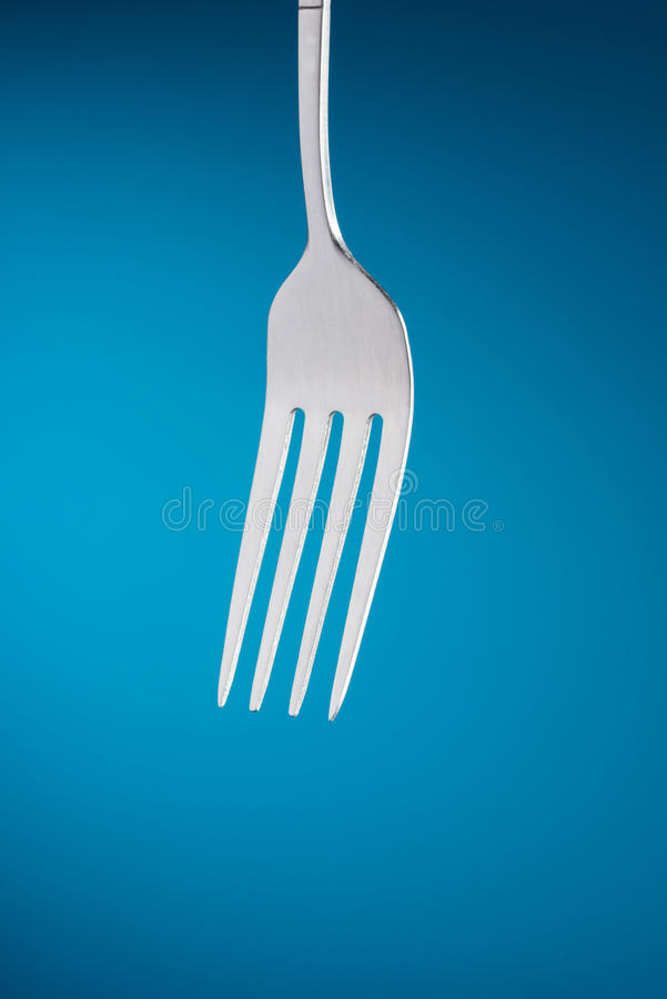 Fork in blue background royalty free stock photo