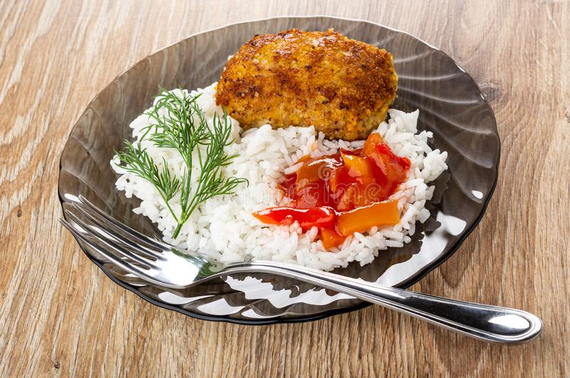 Fork in brown plate with fried patty, rice, lecho, dill on table. Fork in transparent brown plate with fried patty, rice, lecho, dill on wooden table stock photography