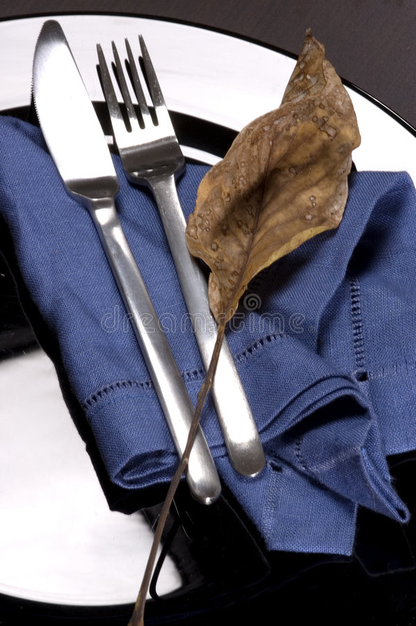Fork and knife. On a black plate with autumn leaf stock images