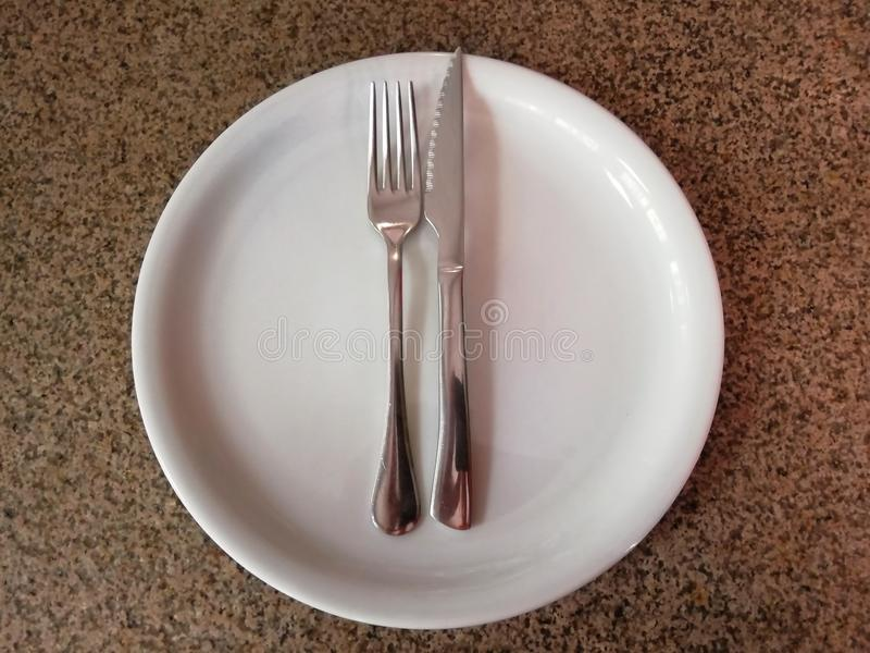 Fork and knife on a empty plate royalty free stock image