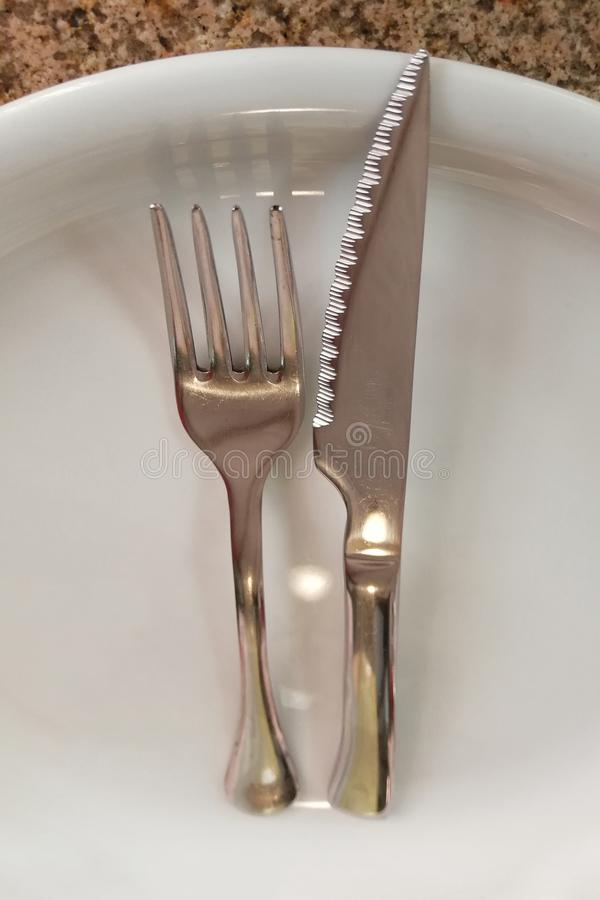 Fork and knife on a empty plate stock photography