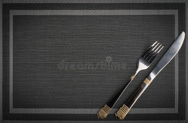 Fork and Knife with golden elements on a placemat stock photo