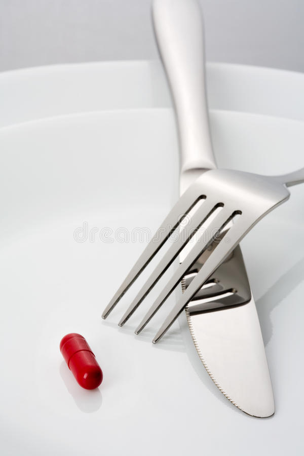 Fork, knife and a single red pill on a plate. Close up stock image