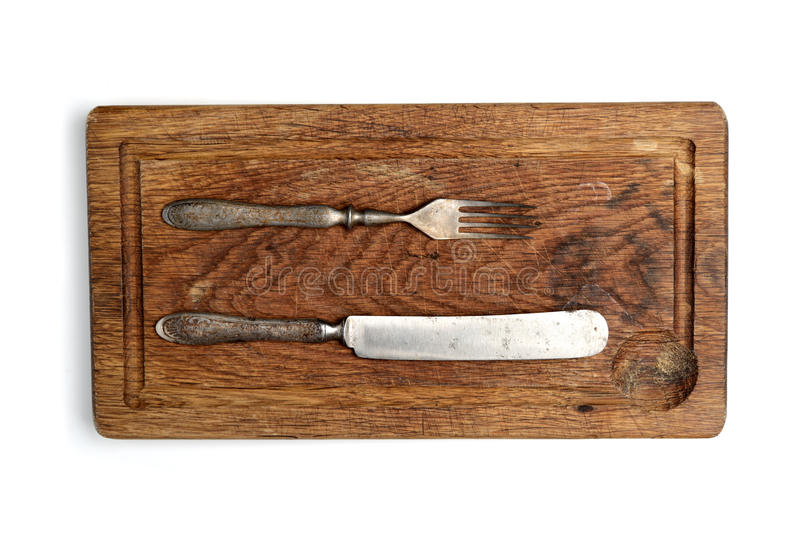 Fork, knife in vintage style on an old cutting board on a white background royalty free stock image