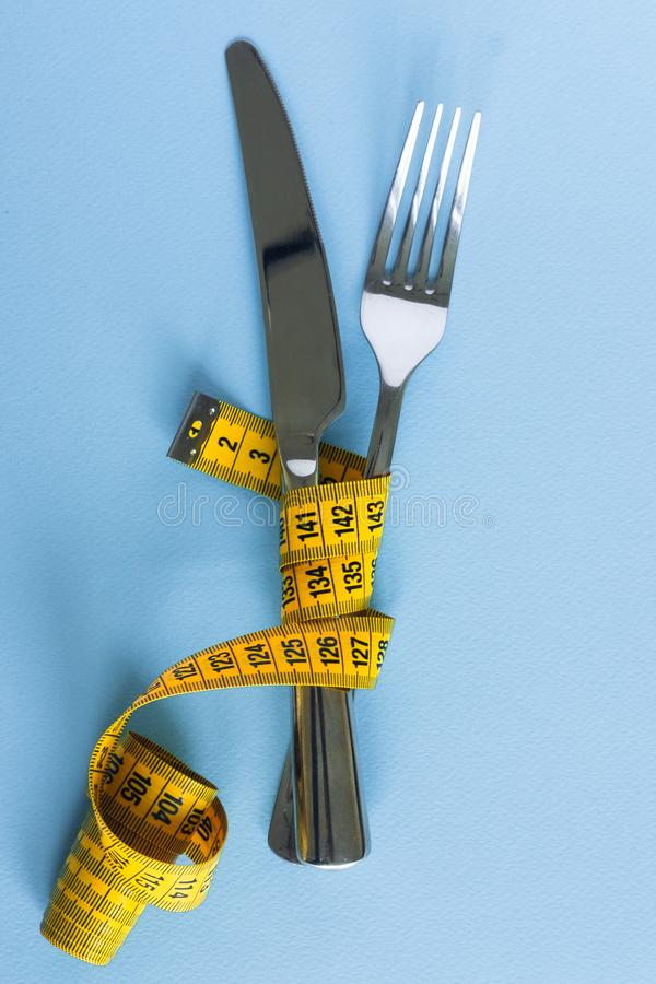 Fork and knife wrapped in tape-line on blue background. Diet concept. royalty free stock photo
