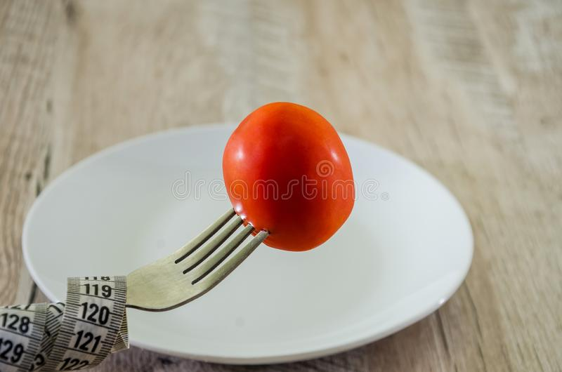 Fork with measuring tape, tomato and plate. Diet concept. Close-up. stock photo