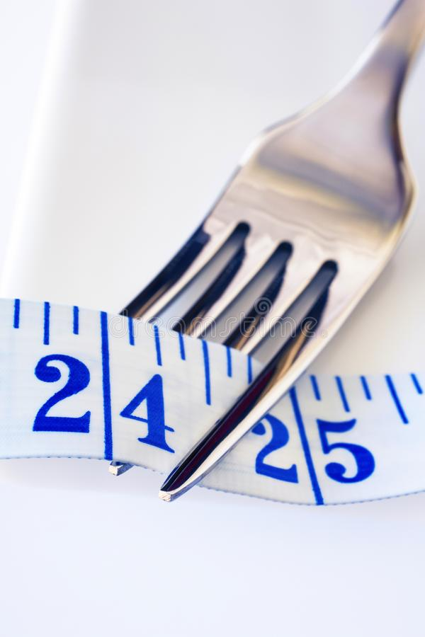 Fork and Tape Measure Showing 24 Inches. Fork resting on a white plate with imperial tape measure entwined in its prongs, showing 24 inches, and copy space stock images