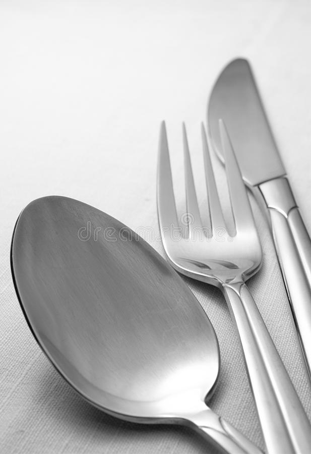 Fork, spoon and knife on a napkin. On the table royalty free stock image