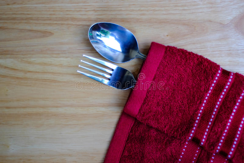 Fork and spoon on red napkin. Vintage fork and spoon on red napkin and wood table stock photography