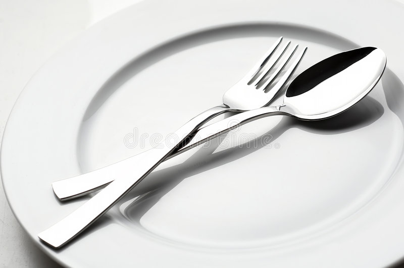 Fork and spoon on white plate stock image
