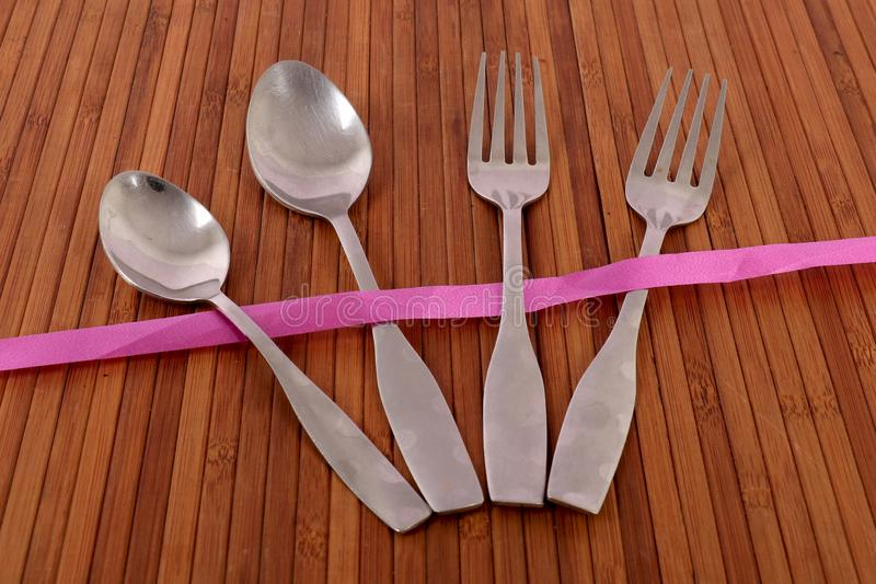 Fork and spoons. Beautiful shot of fork and spoons on wooden background royalty free stock image