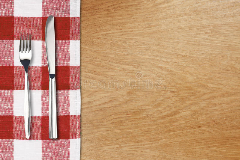 Fork and tableknife on red gingham tablecloth. Wooden table top view royalty free stock photos