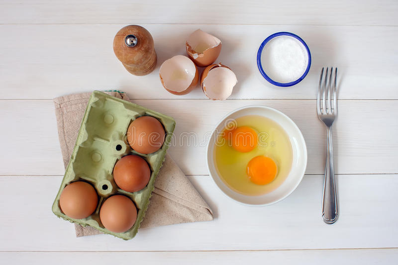 Fork for whipping eggs and raw eggs in a bowl royalty free stock photo