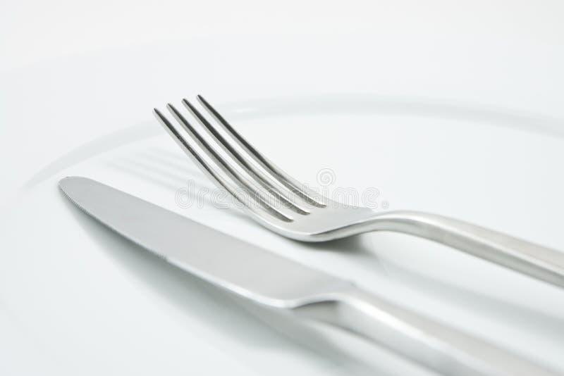 Fork y cuchillo en la placa blanca imagen de archivo libre de regalías