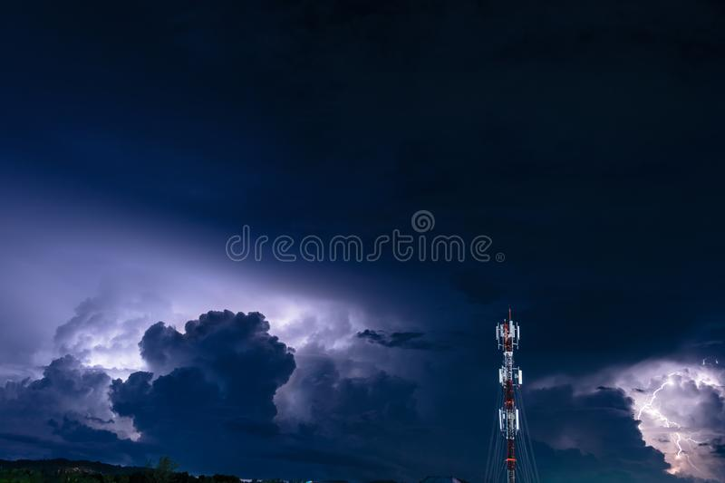 Forked lightning over the cell phone antenna tower at night stock photography