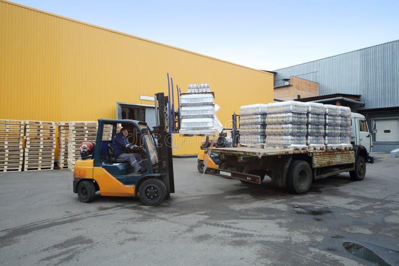 Forklift παλέτες φόρτωσης των μπουκαλιών μπύρας στο φορτηγό στοκ εικόνες