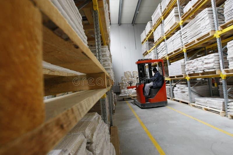 Forklift που λειτουργεί σε μια ξύλινη αποθήκη εμπορευμάτων στοκ εικόνα