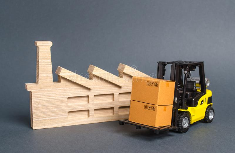 Forklift carries cardboard boxes and building a factory or plant. Services transportation of goods products, logistics. In the industry, economic relations stock photography