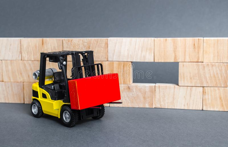A forklift carries a red block to insert into a wall void. A key element to complete the project, part of the whole. Innovation royalty free stock image