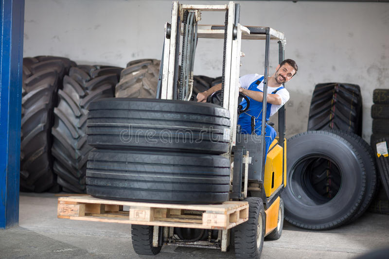 Forklift carries sell car tires royalty free stock photo