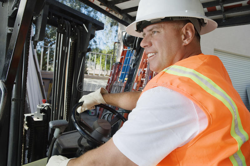 Forklift Driver. Happy male industrial worker driving forklift at workplace stock image