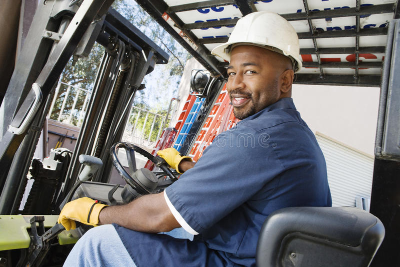 Forklift Driver. Portrait of a happy African American male worker driving forklift at workplace royalty free stock photo