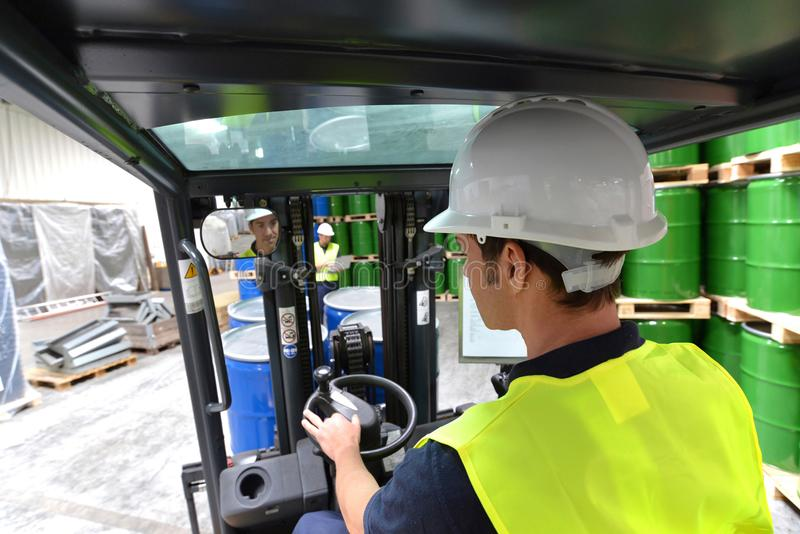 Forklift driver in a logistics hall of a chemical warehouse. Closeup royalty free stock image