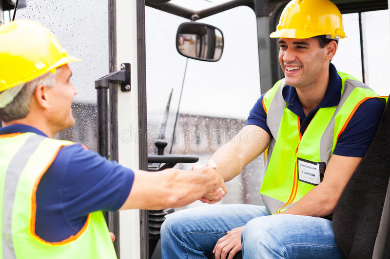Forklift drivers handshaking. Two warehouse forklift drivers handshaking when shift change over royalty free stock photos