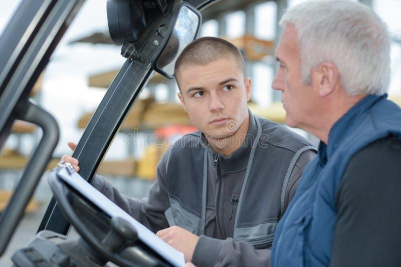Forklift kierowca w przemysłowych logistyk magazynie z współpracownikiem fotografia royalty free