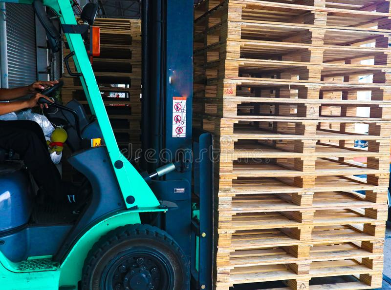 Forklift operator handling wooden pallets in warehouse cargo for transportation to customer factory stock image