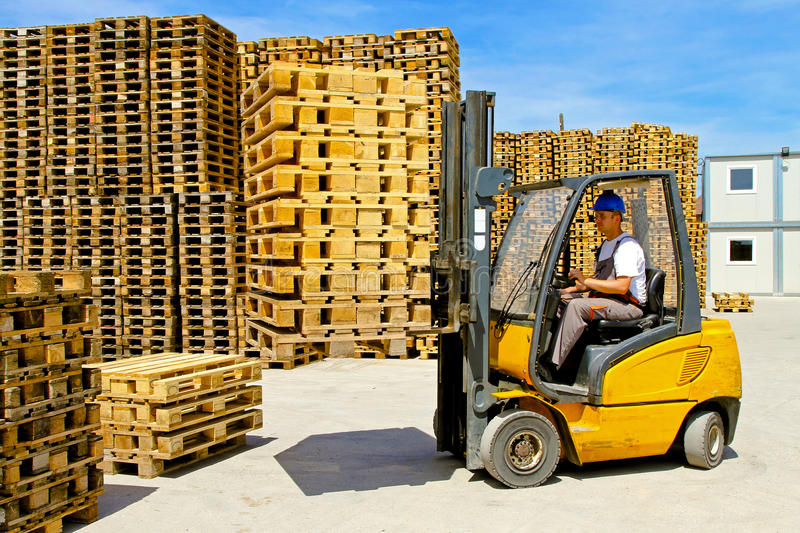 Forklift pallets. Forklift operator handling euro pallets in warehouse royalty free stock image