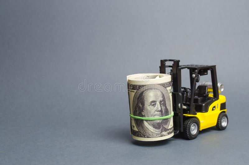 Forklift truck carries a bundle of dollars. Attracting direct investment in business and production, improving economic royalty free stock photography