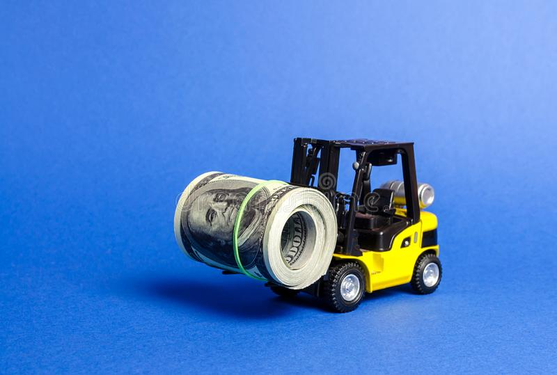 Forklift truck carries a bundle of dollars. Export of capital, offshore economic zones. Attracting direct investment in business stock photo