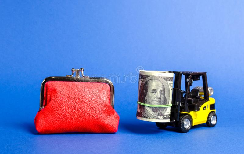 Forklift truck carries a bundle of dollars near a big red wallet. Loan portfolio and investment groups. Savings and deposits stock photos