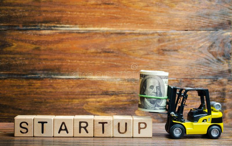 Forklift truck carries a bundle of dollars to inscription Startup. The concept of raising funds for a startup. Crowdfunding royalty free stock photography