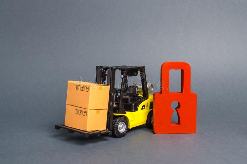 Forklift truck carries a cardboard box next to red padlock. Embargo, trade wars. No delivery. Restriction on the importation. Of goods, proprietary for business royalty free stock images
