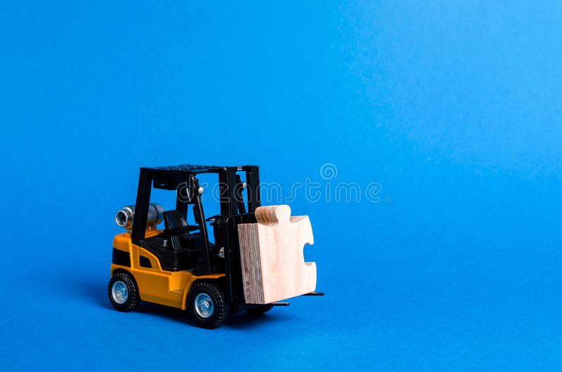 Forklift truck carries part of the puzzle. Business processes and globalization concept. Take a Niche Market. Take part in a large royalty free stock photo