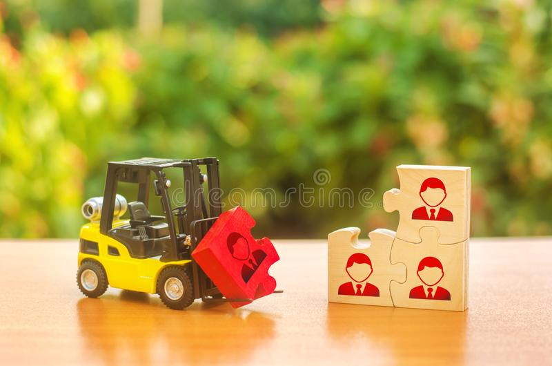 A forklift truck carries a red puzzle to the unfinished assembly of business team. Search, recruitment staff, hiring leader. Creating an efficient and stock photography