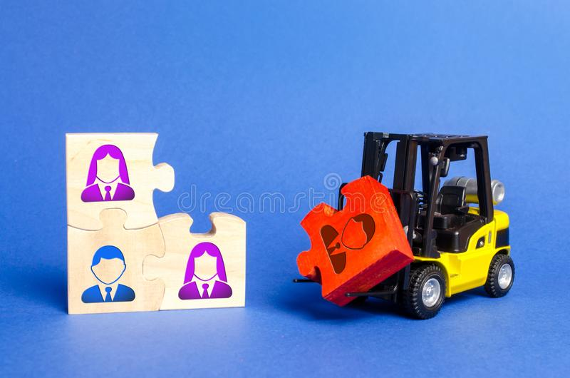 A forklift truck carries a red puzzle to the unfinished assembly of business team. Search, recruitment staff, hiring leader. Creating an efficient and royalty free stock image