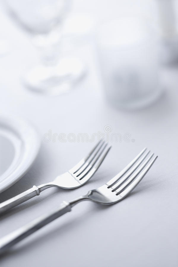 Forks on Dining Table. Two forks sitting side-by-side on a dining table with white tablecloth. Vertical shot royalty free stock photography
