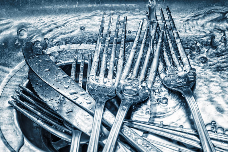 Forks and knives washed on a kitchen sink royalty free stock images