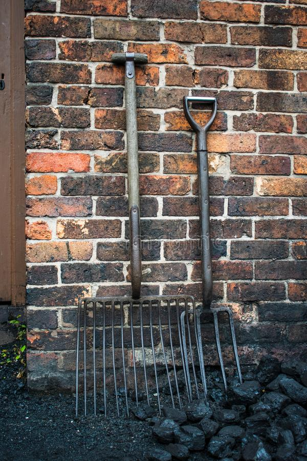 Old forks for moving coal, outside a colliers house. Loose coal would be moved by a fork or shovel into a sack ready to sell stock photography