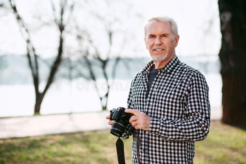 Glad senior man doing photography stock photo